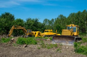 Excavator and bulldozer clearing forest land. Heavy equipment.